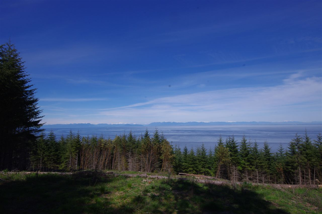 View across the Strait of Georgia from the Vancouver coast line to the Sunshine Coast. 4.97 acre treed lot in Panorama Estates with view and potential building site cleared. Lot has driveway in from Panorama Lane (a private access easement). A 3 gallon per minute well. RR zoning allows for the building of a home and cottage. Panorama Estates borders Bodega Ridge Park.
