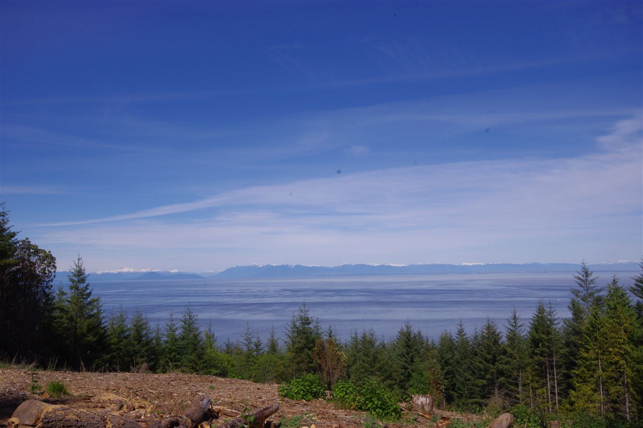 View across the Strait of Georgia from the Vancouver coast line to the Sunshine coast. 4.97 acre treed lot in Panorama Estates with view and potential building site cleared. Lot has driveway in from Panorama Lane (a private access easement). A 6 gallon per minute well. RR zoning allows for the building of a home and cottage. Panorama Estates borders Bodega Ridge Park.