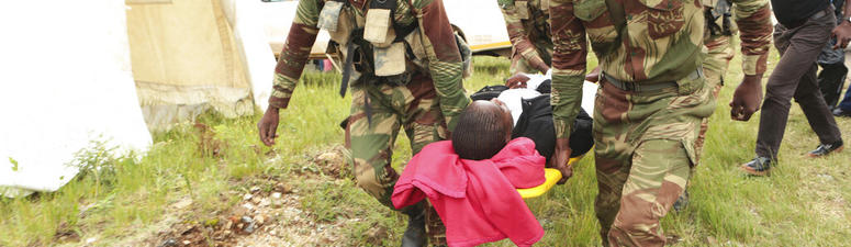 Soldiers carry injured survivors from a helicopter in Chimanimani about 600 kilometres south east of Harare, Zimbabwe, Tuesday, March, 19, 2019. AP Photo/Tsvangirayi Mukwazhi)