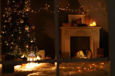 Stylish living room interior with decorated Christmas tree and fireplace at night, view through window