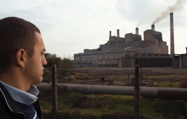 Kosovo citizen looks at aging coal-fired power plant. Photo Credit: Lum Citaku
