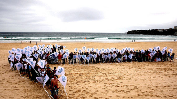 hundreds of 350 supporters forming an arrow on Bondi Beach in Australia.