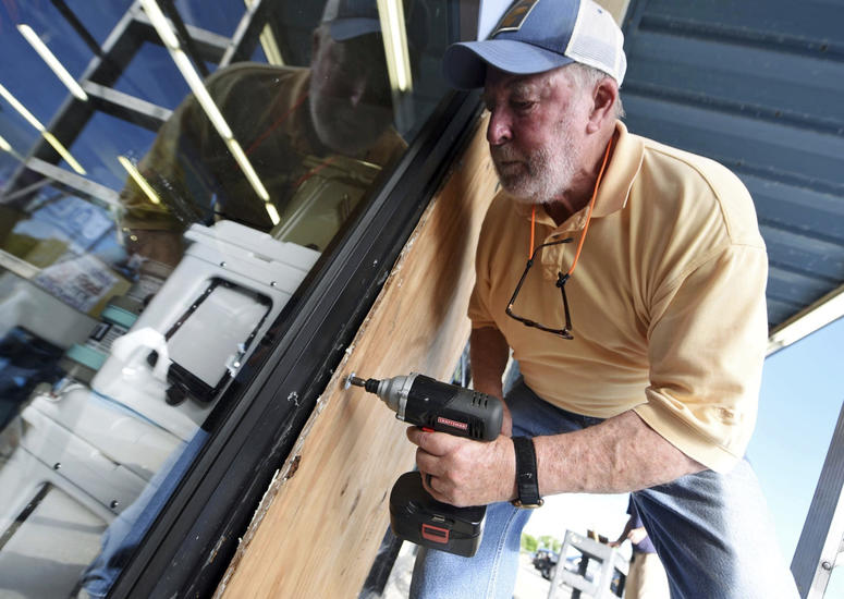 Garland Meadows of Redix boards up the front windows of the store in Wrightsville Beach, N.C., Tuesday, Sept. 11, 2018. Mandatory evacuations were imposed for parts of several East Coast states Tuesday as millions of Americans prepared for what could beco