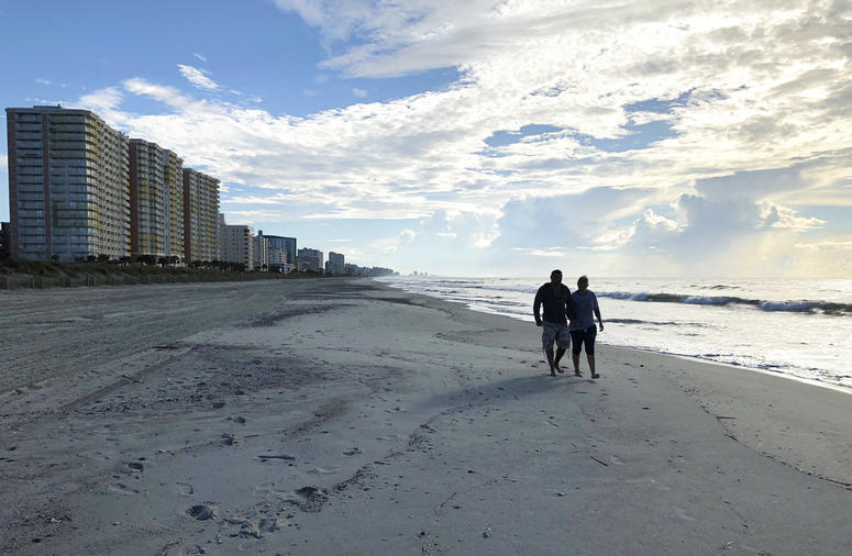 Chris and Nicole Roland walk down a beach in North Myrtle Beach, S.C. on Wednesday, Sept. 12, 2018. The couple boarded up their uncle's condominium and are leaving soon as Hurricane Florence approaches