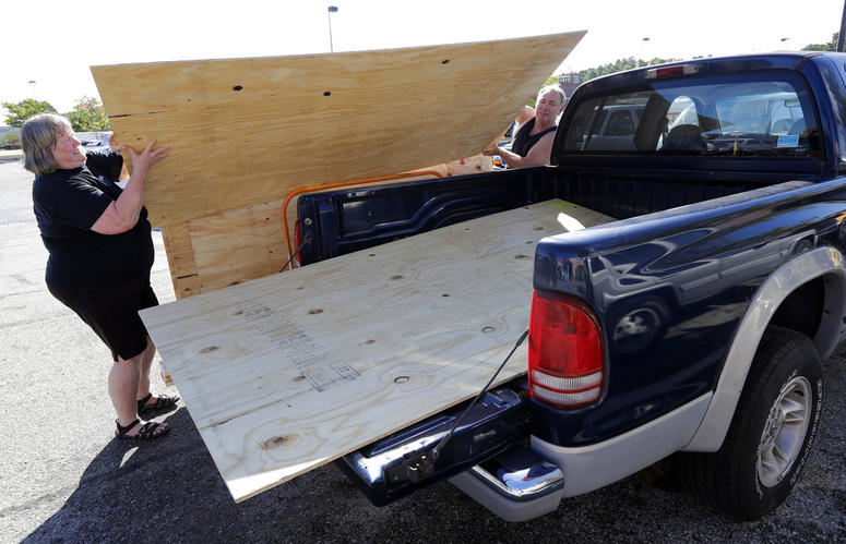 Mickey Manes, right, and Diane Manes, left, load plywood into their truck in advance of Hurricane Florence in Wilmington, N.C., Wednesday, Sept. 12, 2018. Florence exploded into a potentially catastrophic hurricane Monday as it closed in on North and Sout