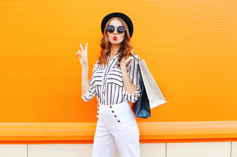 Fashion young girl with shopping bags wearing a black hat white pants over colorful orange