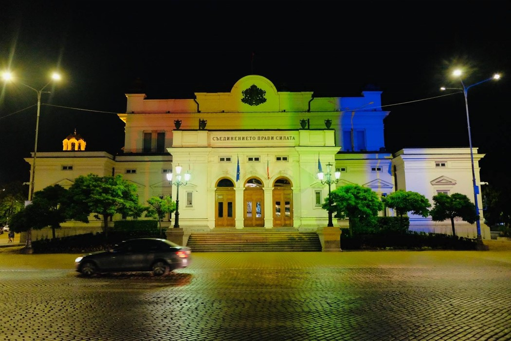 Das Foto zeigt das nationale Parlamentsgebäude in Sofia, Bulgarien, beleuchtet mit Regenbogenfarben.