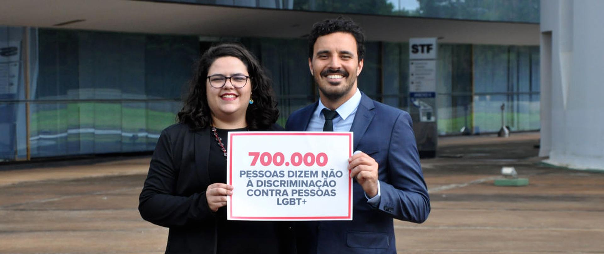 Duas pessoas seguram um cartaz dizendo 700 mil pessoas dizem não à discriminação contra pessoas LGBT+