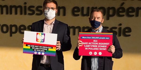 La foto mostra Matt Beard e Marcin Rodzinka con i messaggi della campagna sui cartelli davanti alla Commissione Europea