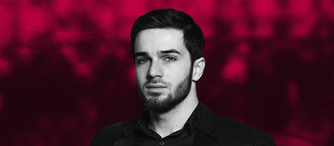 Picture of Zelim Bakaev in black and white over a dark pink background.