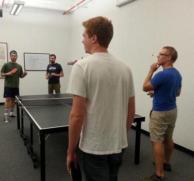 Photo of four people playing ping pong