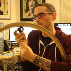 Josh sawyer removing spokes from a bicycle wheel.