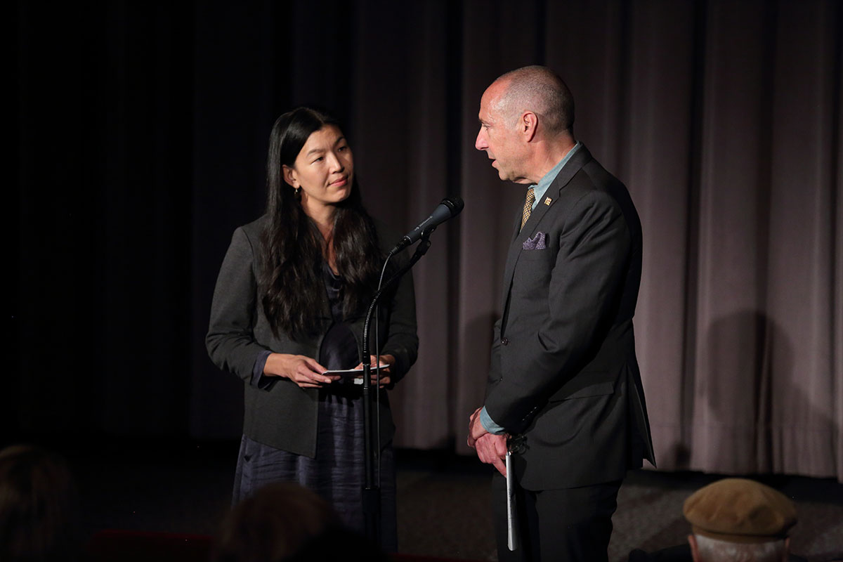 Ai-jen Poo and Bob Beitcher stand at a microphone