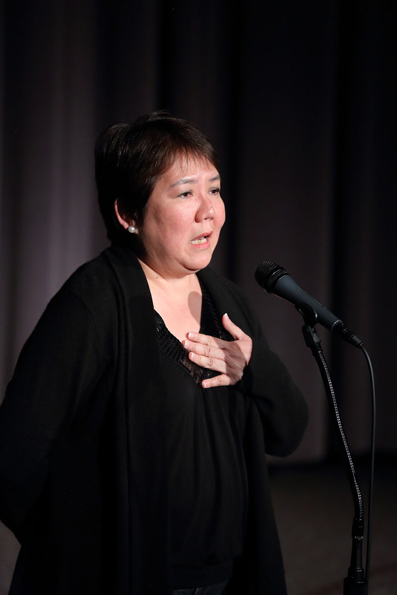 A women covers her heart while standing at a microphone