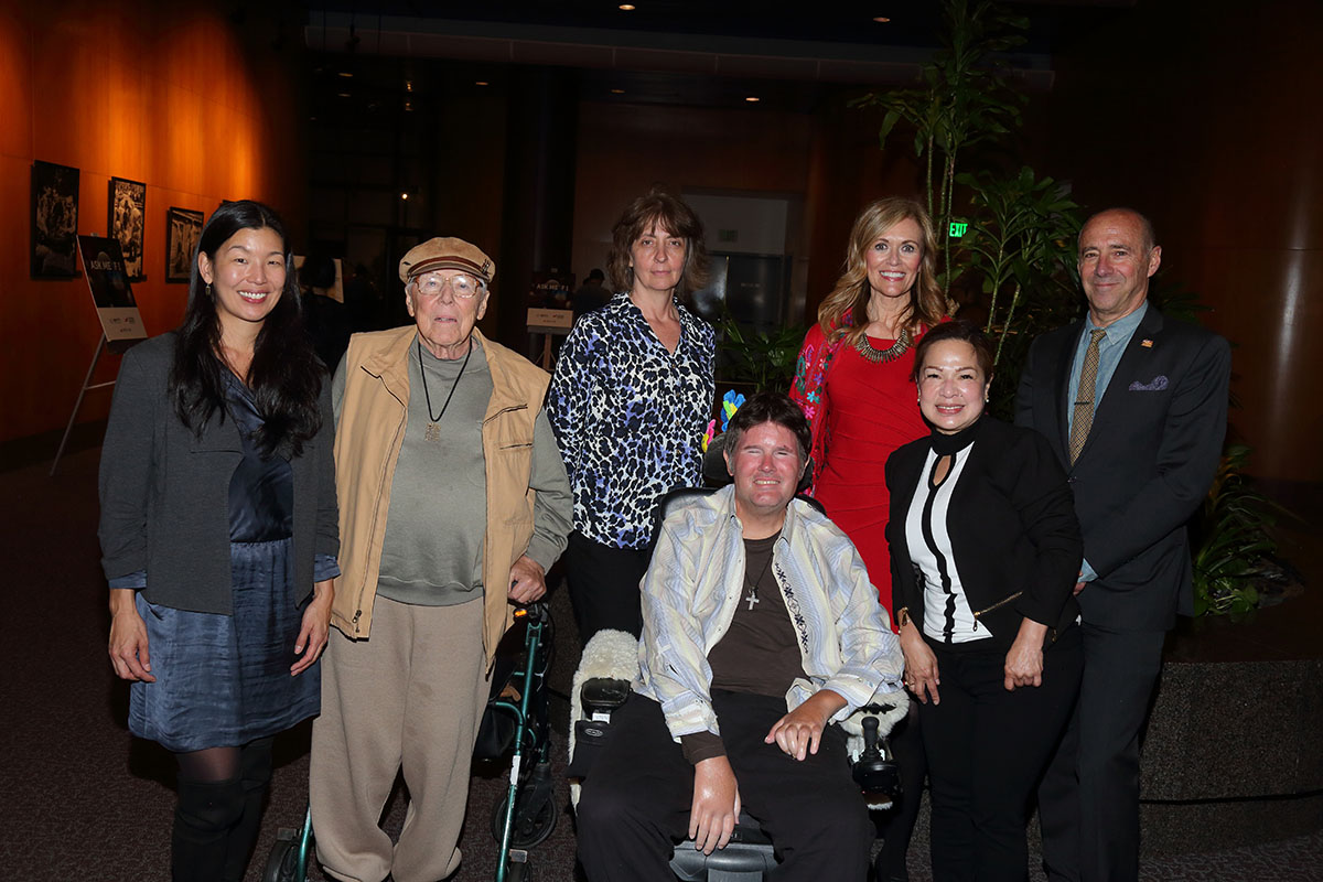 Ai-jen Poo and Bob Beitcher stand with five other people, one who is in a wheelchair and one who is using a walker
