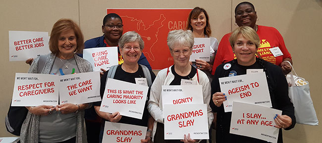 Women pose with signs demanding respect for caregivers at the Caring Across photo booth at the We Won't Wait Summit