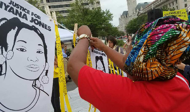 A woman places a memorial ribbon during the vigil at the We Won't Wait Summit
