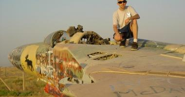 Blad Air Base Andrew Koehle sits atop a derelict Russian MiG fighter
