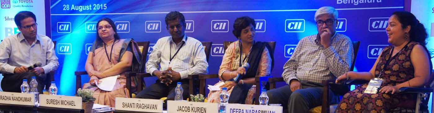 A banner running from left to right of the screen is a picture from a conference. A blue banner is at the background with CII on it. A panel of two men and two women, all seated, is on stage, two of them holding mikes.