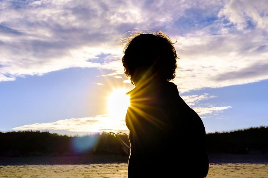 Child walking toward the sun on the beach