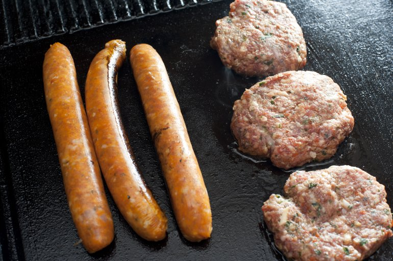 Beef patties and sausages on a barbecue