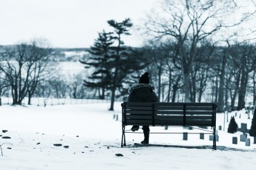 Woman seated on a park bench in winter