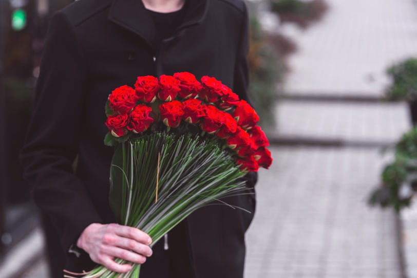 Young man holding one big beautiful bouquet of many red rose flowers ...