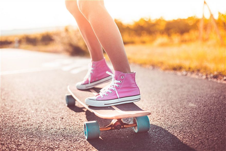 Young Girl with Pink Shoes Riding a Longboard