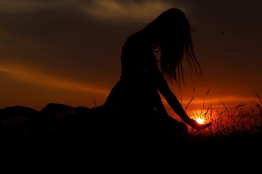 Beautiful Woman Silhouette at sunset holding sun