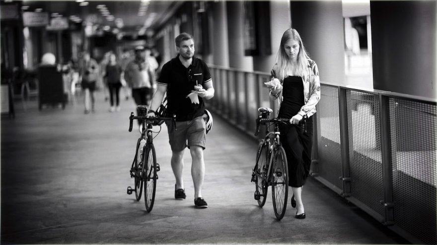 Black and White of two people walking their bikes