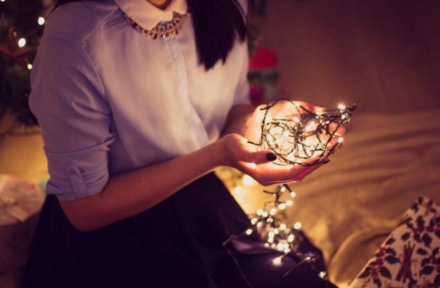 girl holds christmas lights