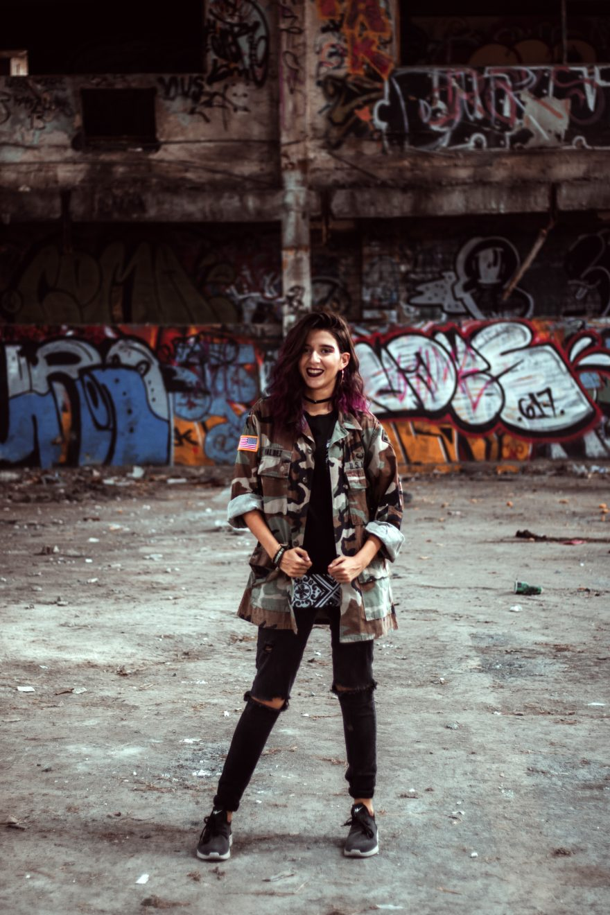 Woman in army jacket standing