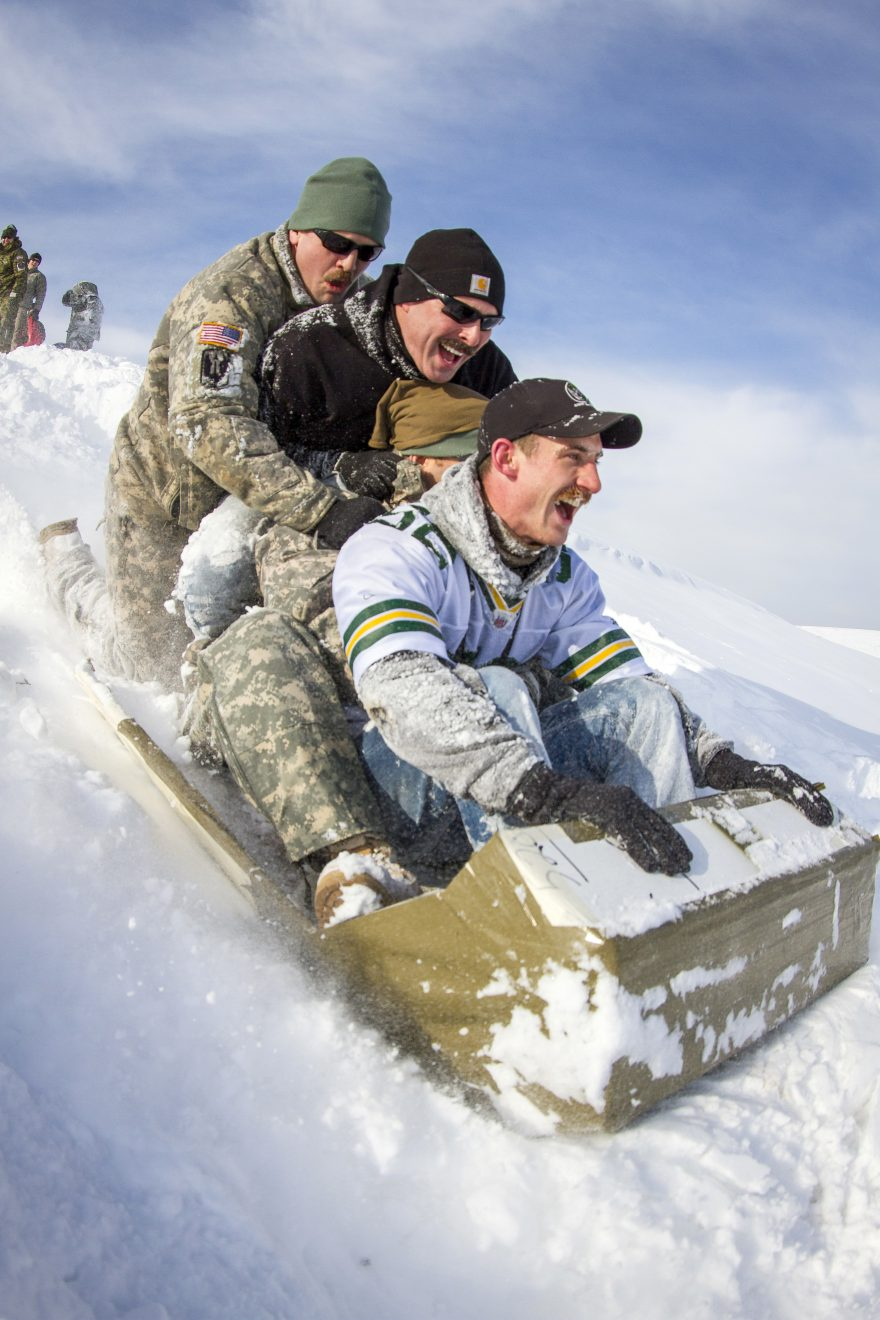 Three guys going down a hill on a sled