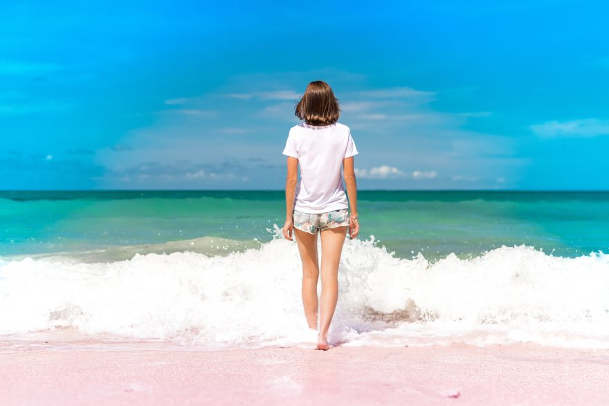 Young woman walking into the waves of the ocean on beach