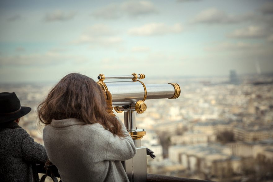 Woman looking at city through telescope