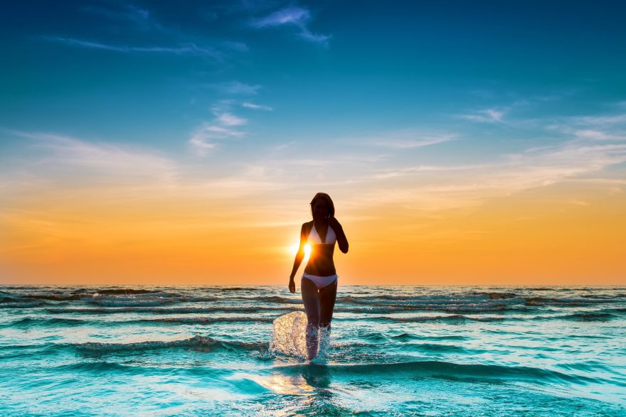 Woman in bathing suit walking in the ocean