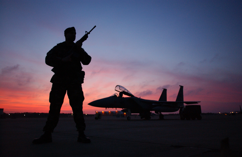 Soldier standing guard over fighter plane