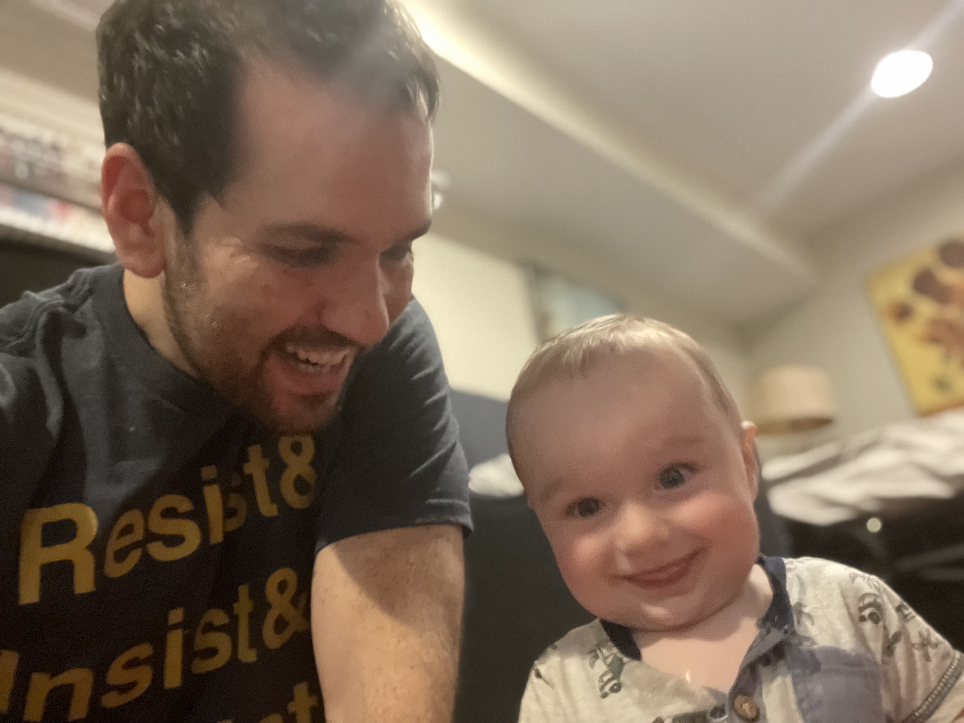 Ezra and Zeke sitting on the floor together. Zeke is smiling at the camera with his tongue stuck out and Ezra is wearing a Resist tshirt.