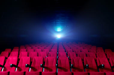 Movie theatre hall with red seats and working projector with beams of light
