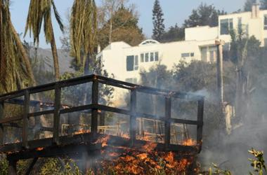 Nov 11, 2018; Malibu, CA, USA; A deck burns at 30111 Harvester Road in Malibu. The neighborhood was over run by the Woosley Fire which has consumed over 70,000 acres as of Nov 10.