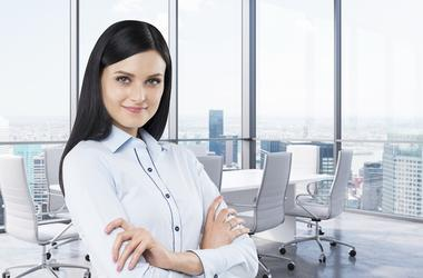 Brunette in a corner conference room. Modern office with huge windows and amazing New York panoramic view.