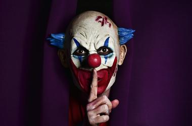 Scary evil clown asking for silence