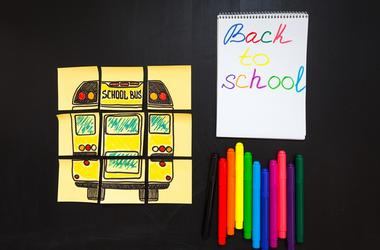 Back to school background with title `Back to school` and `school bus` written on the yellow pieces of paper, notebook with title