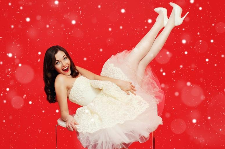 Christmas beautiful brunette bride woman in white wedding dress having fun on the table over colorful red background