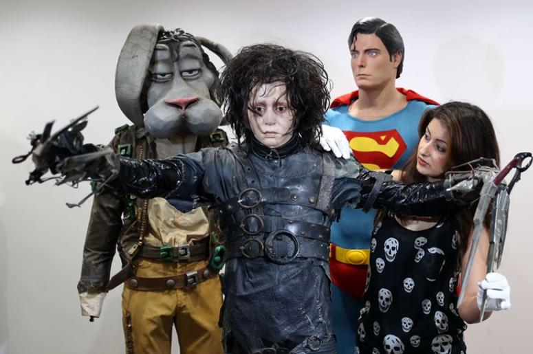 7/30/2018 - Prop Store employee Priya Mudgil (right) adjusts the costume of Edward Scissorhands (estimate £60-80,000) on display next to Christopher Reeve's Superman costume and Michael Jackson's 'Spike' costume from Moonwalker, at the Prop Store he