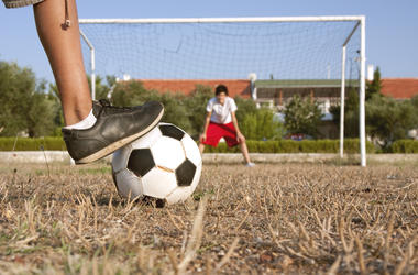 An amateur player is going to shoot a penalty to the goal on a poor soccer pitch