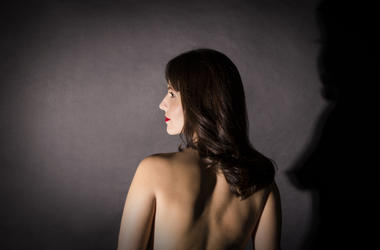 Portrait of naked woman with long hair. Dark, nude.