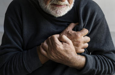 An elderly man is having a heart attack with chest pain