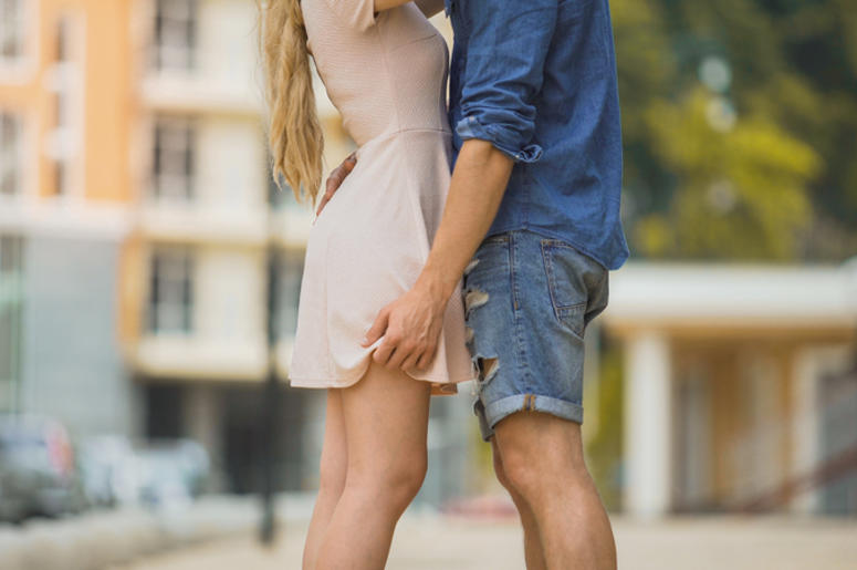 Couple passionately embracing in city street, tender relationship, safe sex