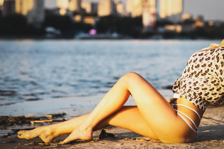 Beautiful happy young woman stands in a bikini with her hands up at the sea background at the sunset